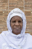 African woman sitting in front of her house, sixty-five years old Royalty Free Stock Photos