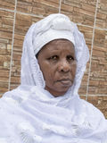 African woman sitting in front of her house, sixty-five years old Royalty Free Stock Image