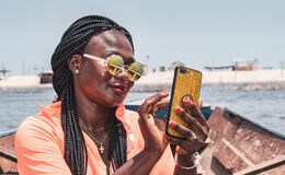 Free African Woman Sitting On A Boat With Mobile Phone In Hand And Taking Photos. The Location Is Accra Ghana West Africa Royalty Free Stock Photos - 182378938