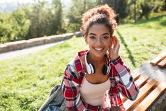 African woman sitting outdoors in park. Royalty Free Stock Photography