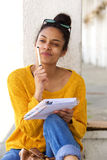 African woman sitting outside thinking and writing in book. Portrait of young african woman sitting outside thinking and writing in book Royalty Free Stock Images
