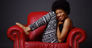 African woman sitting in red armchair Royalty Free Stock Photos