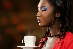 African woman smelling coffee with eyes closed. Close up face shot of attractive young african woman smelling coffee aroma with eyes closed.Low key portrait of royalty free stock photo