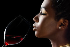 African woman smelling red wine aroma. Macro close up low key portrait of sensual african woman smelling red wine.Side view of girl with red wine glass next to Stock Photography