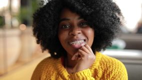 African woman smiling in a cafe. African woman portrait smiling in the cafe close up, slowmotion stock footage