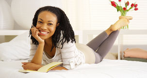 African woman smiling with journal Stock Photography