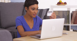 African woman smiling by laptop with credit card Stock Photography