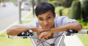 African woman smiling and leaning on bicycle handlebars Stock Image