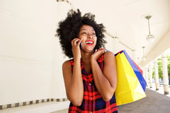 African woman smiling with mobile phone with shopping bags Royalty Free Stock Images