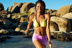 African woman smiling and splashing water at the beach Stock Images