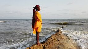 African woman standing on a beautiful beach