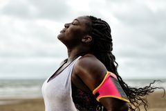 African woman standing under the rain,eyes closed, after workout on beach. African woman standing and enjoying under the rain,eyes closed, after workout on beach royalty free stock photos