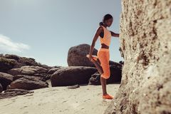 African woman stretching her legs at beach Royalty Free Stock Photos