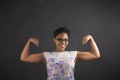 African woman with strong arms on blackboard background Royalty Free Stock Image