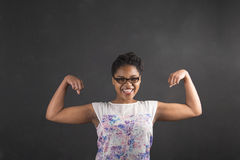 African woman with strong arms on blackboard background Stock Image