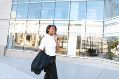 African Woman Student at Library. A pretty african american student woman on the cell phone in front of library stock photos