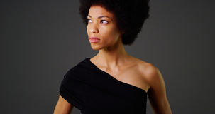 African woman in stylish black dress on grey background Stock Photography