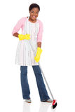 African woman sweeping. Beautiful young african woman sweeping on white background Royalty Free Stock Images