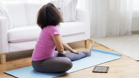 African woman with tablet pc exercising at home