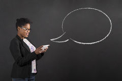 African woman with tablet and speech or thought bubble on blackboard background. South African or African American black woman teacher or student holding a Stock Image