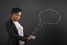 African woman with tablet and speech or thought clouds on blackboard background Stock Images