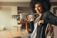 African woman taking coffee break while working from home. Portrait of attractive woman with curly hair having coffee at home with a laptop. African woman taking royalty free stock image