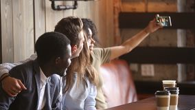 African-american woman taking group selfie at meeting with diverse friends stock footage
