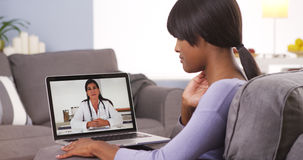 African woman talking with doctor online Stock Photography