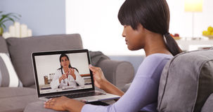 African woman talking with doctor online Stock Photo
