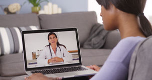 African woman talking with doctor online. Woman talking with doctor online Stock Photography