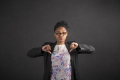 African woman with thumbs down hand signal on blackboard background Royalty Free Stock Photos