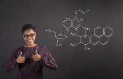 African woman with thumbs up hand signal with science on blackboard background Royalty Free Stock Photography