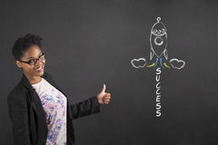 African woman with thumbs up hand signal and success rocket on blackboard background Royalty Free Stock Photos