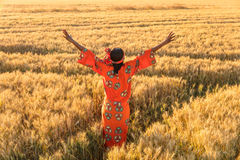 African woman in traditional clothes arms raised in field of cro. African woman in traditional clothes standing arms raised in a field of barley or wheat crops Royalty Free Stock Photo