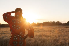 African woman in traditional clothes in a field of crops at suns. African woman in traditional clothes looking across a field of barley or wheat crops at sunset Royalty Free Stock Photo
