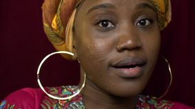 Black woman with gold earrings is surprised at the camera, slow motion stock video footage