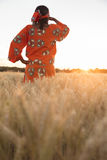 African woman in traditional clothes looking in a field of crops Stock Photos
