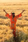 African woman in traditional clothes standing in a field of crop Stock Photos