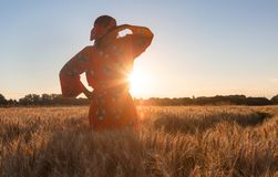 African woman in traditional clothes standing in a field of crop. African woman in traditional clothes standing, looking, hand to eyes, in field of barley or Stock Photo