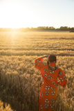 African woman in traditional clothes standing in a field of crop Royalty Free Stock Images