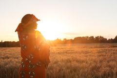African woman in traditional clothes standing in a field of crop. African woman in traditional clothes standing, looking, hand to eyes, in field of barley or Royalty Free Stock Images