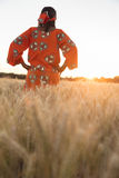 African woman in traditional clothes walking in a field of crops Stock Photo