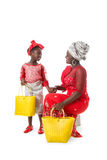African woman in traditional clothing and little girl with tote bags.Isolated Stock Photos
