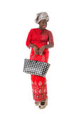 African woman in traditional clothing with tote bag.Isolated. Beautiful African woman in red traditional clothing with wicker tote bag. Isolated on the white royalty free stock image