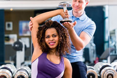 African woman and trainer at exercise in gym Royalty Free Stock Images