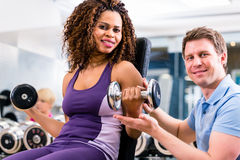 African woman and trainer at exercise in gym Stock Photos