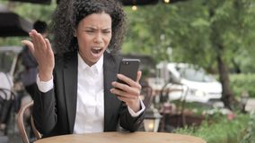 African Woman Upset by Loss on Smartphone, Sitting in Outdoor Cafe stock video footage