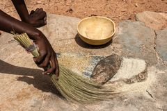 An african woman using her fiber broom. After having ground cereals millet/sorghum in Burkina Faso. Tools : grindstones, fiber broom, calebash stock photos