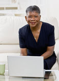 African woman using laptop on sofa at home. Mature African woman using laptop on sofa at home Royalty Free Stock Photo
