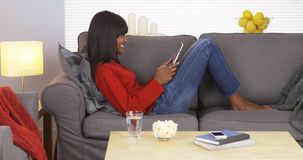 African woman using pad on couch Stock Photo
